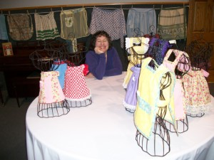 Ellie at an event in Monmouth, Illinois posing with mounted aprons and miniature apron centerpieces